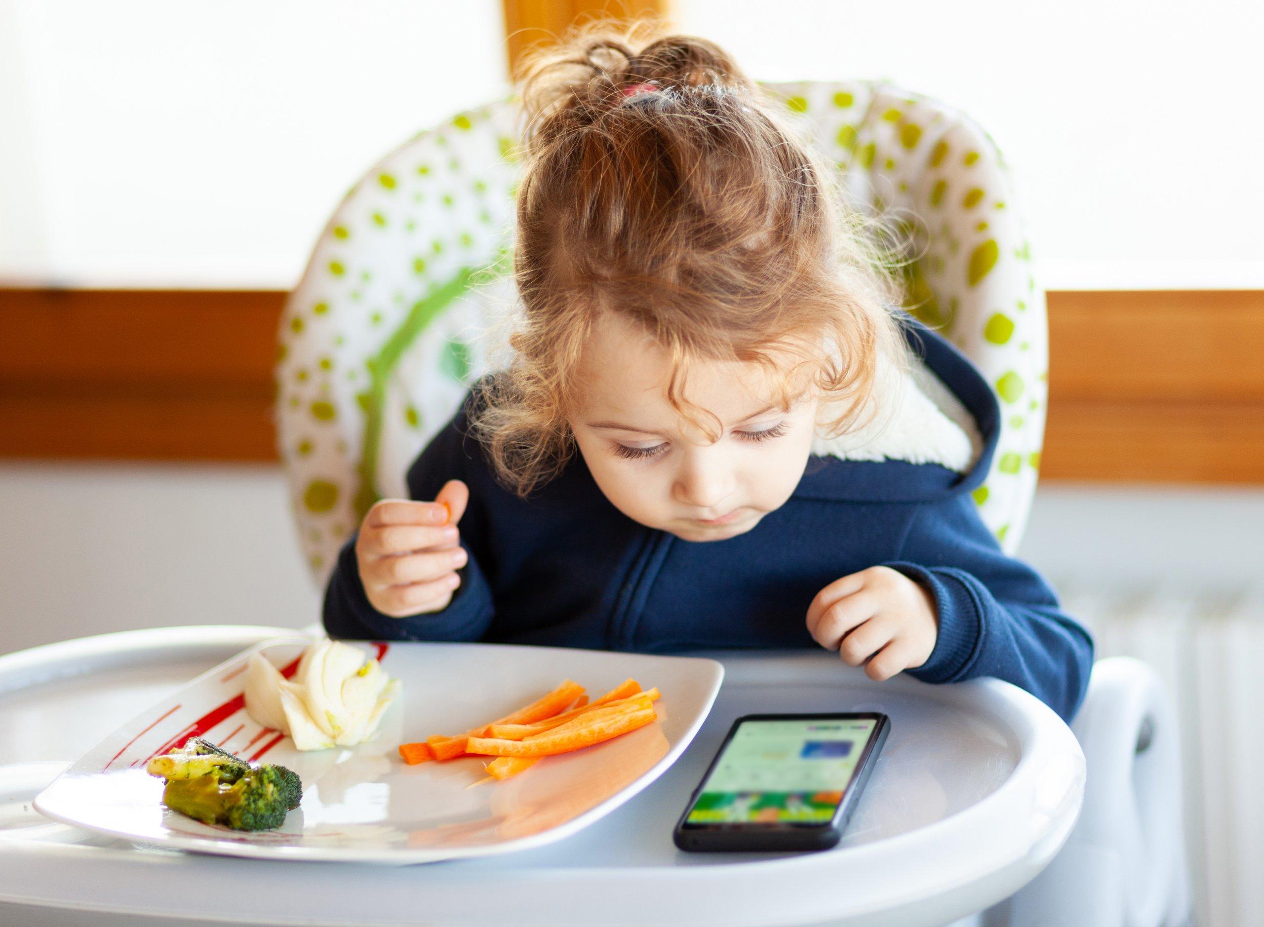 Niña comiendo con el móvil